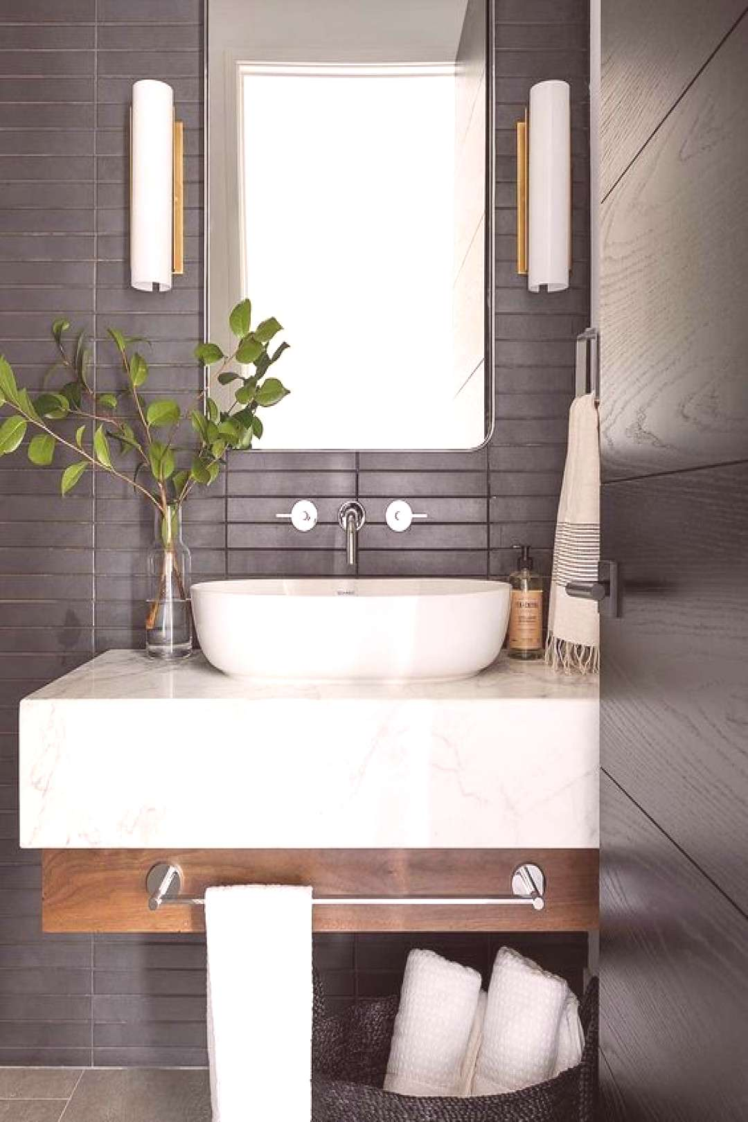 a contemporary bathroom with matte black skinny tiles on the wall plus a floating wood and marble v