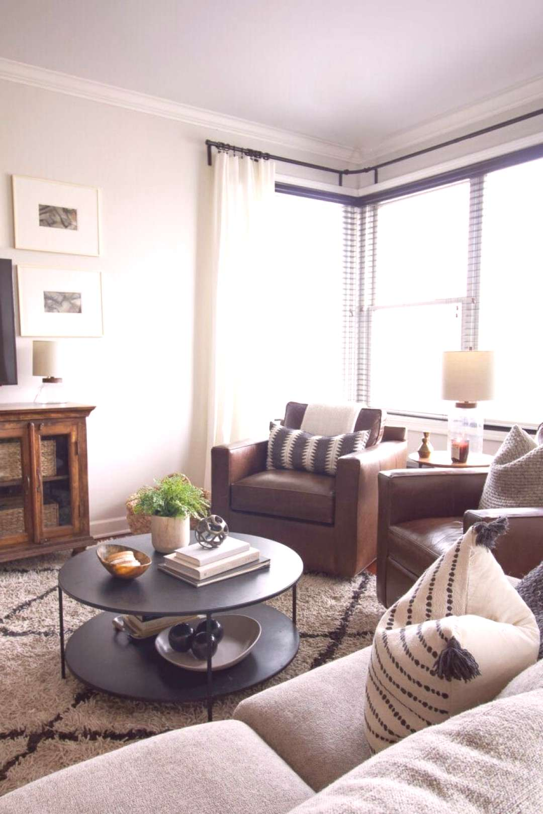 Curtains and leather chairs in the living room. Come take a look at this family-friendly home tour.